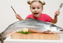 enfant-mange-gros-poisson-photo